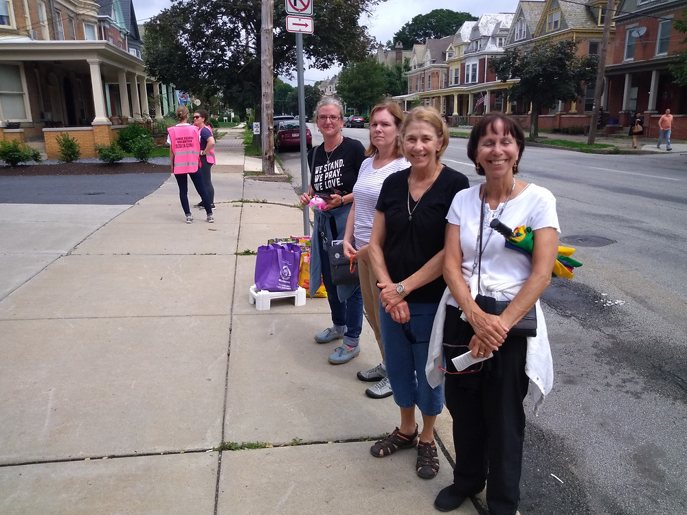 Four volunteers with Undefeated Courage stand on the curb of the sidewalk offering free resources to those going in or out of Planned Parenthood.