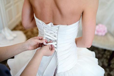 bridesmaid-is-lacing-white-wedding-dress
