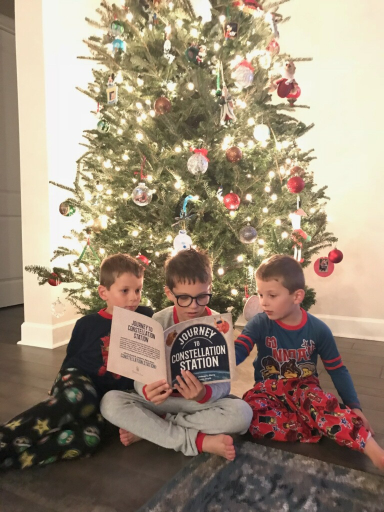 Three young boys reading Journey to Constellation Station in front of a Christmas tree