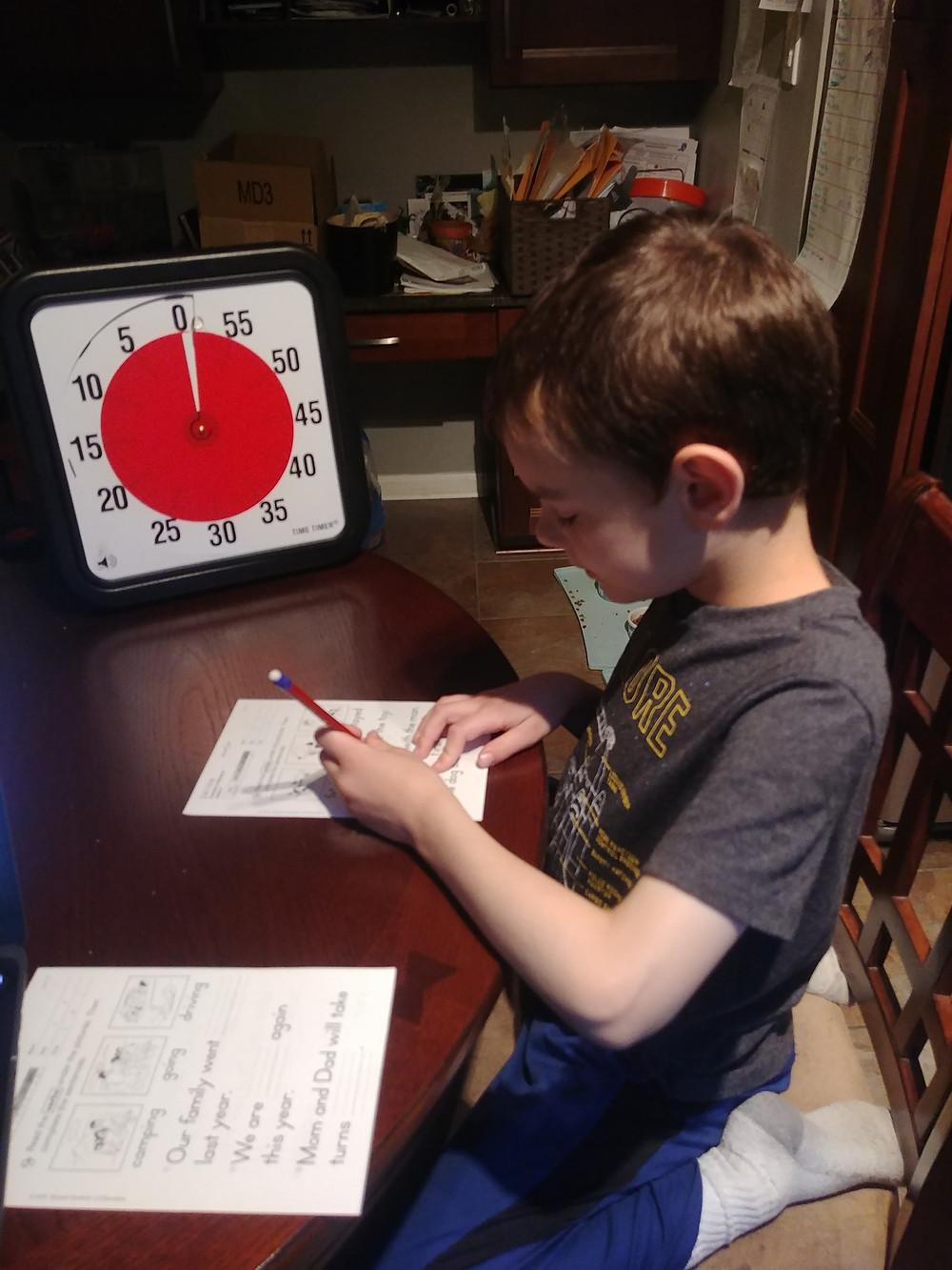 Boy next to a visual timing doing homework