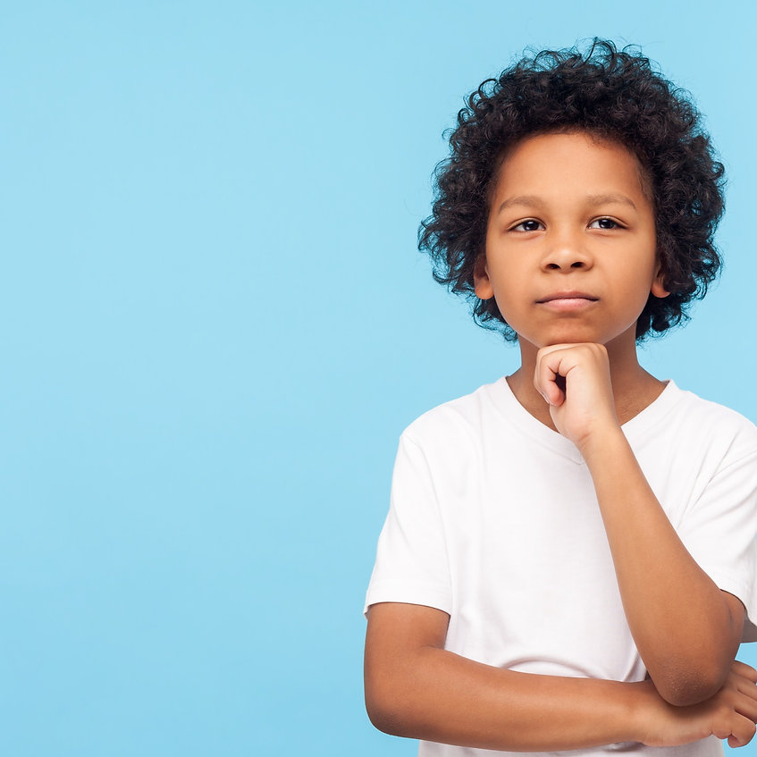 Let me think! Portrait of pensive clever curly preschooler in T-shirt standing with puzzle