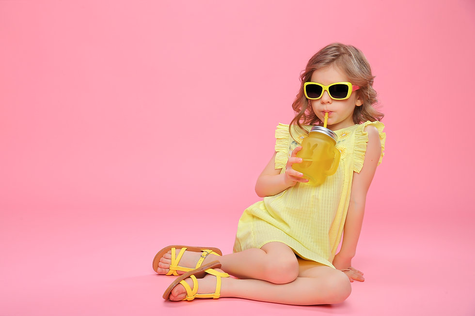 Pretty little girl in dress and sunglasses sitting on pink with glass jar of cocktail chil