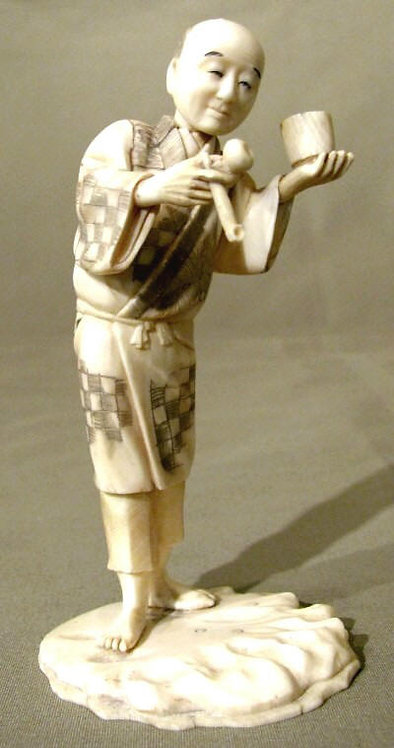 A Finely Carved Okimono of a Man Holding an Opium Pipe,Japanese, Meiji Period
