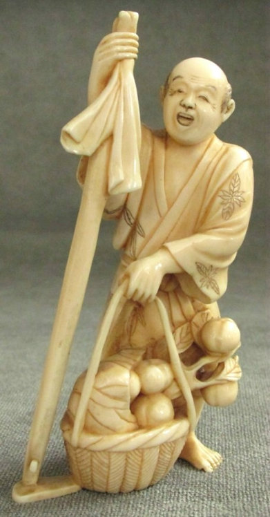A Very Good Japanese Ivory Okimono of a Fruit Vendor, Meiji Period (1868-1912)