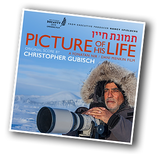 Amos Nachoum is holding his camera in the snow. Picture of His Life is a documentary film.