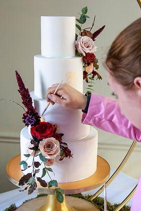 Charlotte Wilcox gilding an elegant white wedding cake.