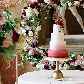 A red ombre wedding cake with fresh flowers at Wentworth Woodhouse