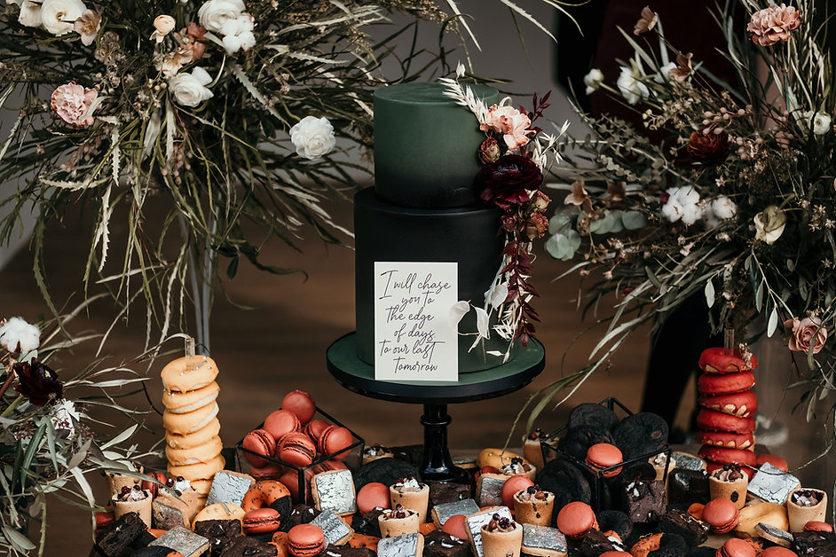 A luxury gothic wedding cake and dessert table with dried flowers at The Harewood Estate