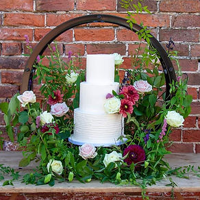 A buttercream wedding cake in a hoop of fresh flowers