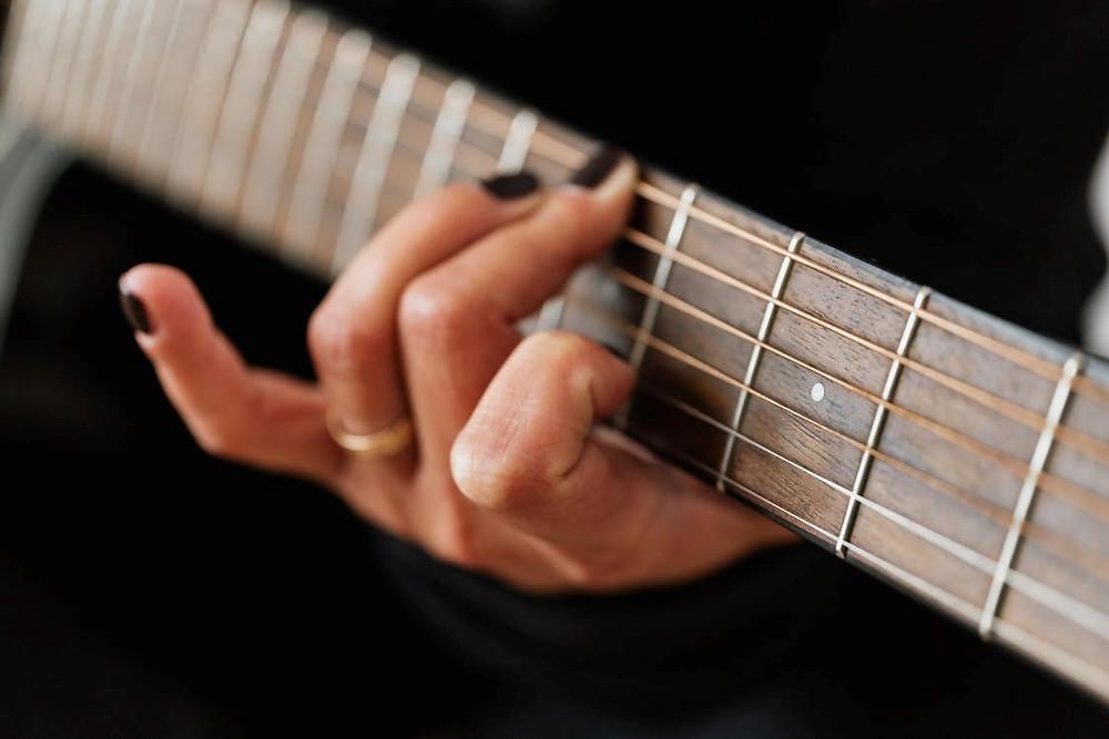 Closeup of a woman's hands playing guitar.