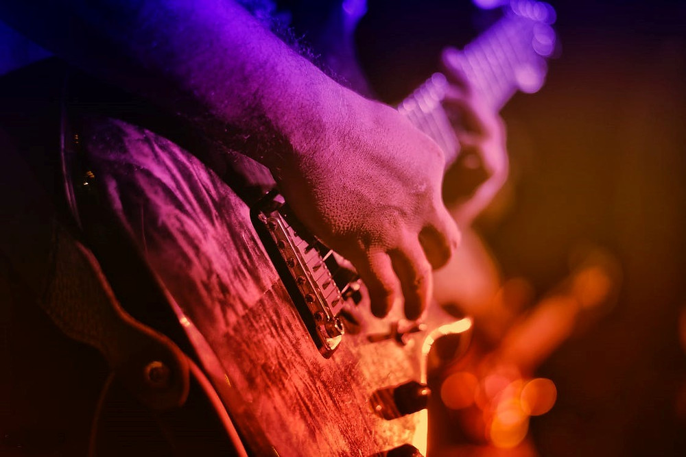 Closeup of a guitarist playing his instrument while on stage.
