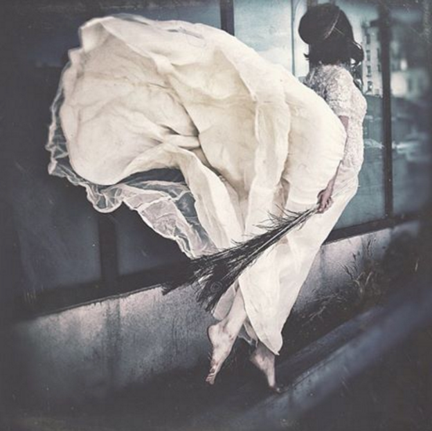 A woman in a white dress alights like an angel.
