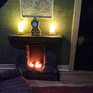 Candles on the mantle and glowing embers in the fireplace