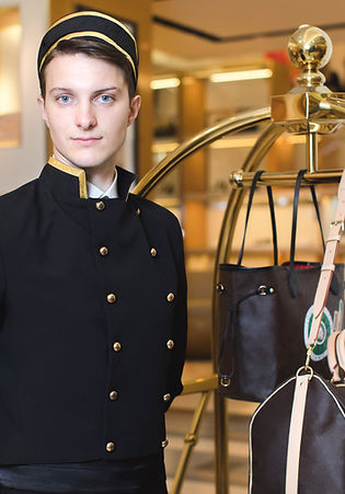 Young man in uniform serving in hotel.jp