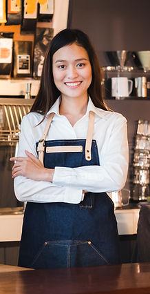 Asian female barista wear jean apron cro