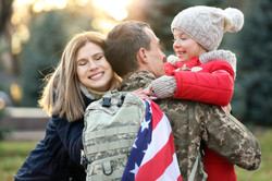USA soldier hugging his family outdoors