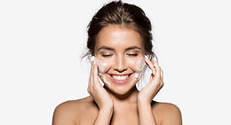 Happy smiling lady washing her face.