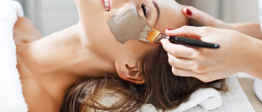 Smiling lady at beauty salon have a beauty facemask applied