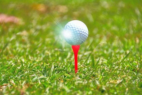 Golf ball on orange tee.