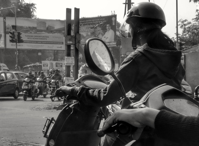 Pune, 2016. Most single women in Pune wore helmets while riding scooters. Men not so much (as seen in the background here). Taken from the back of a taxi using a Sony DSC-RX100