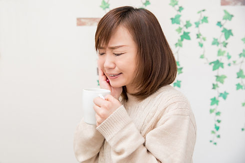 歯を押える女性
