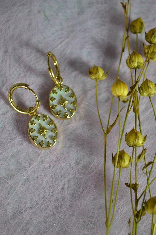 goudkleurige oorbellen met witte hangers