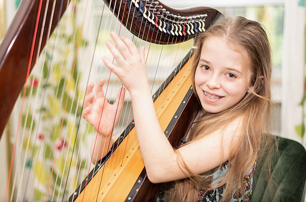 A young girl plays harp and looks at the