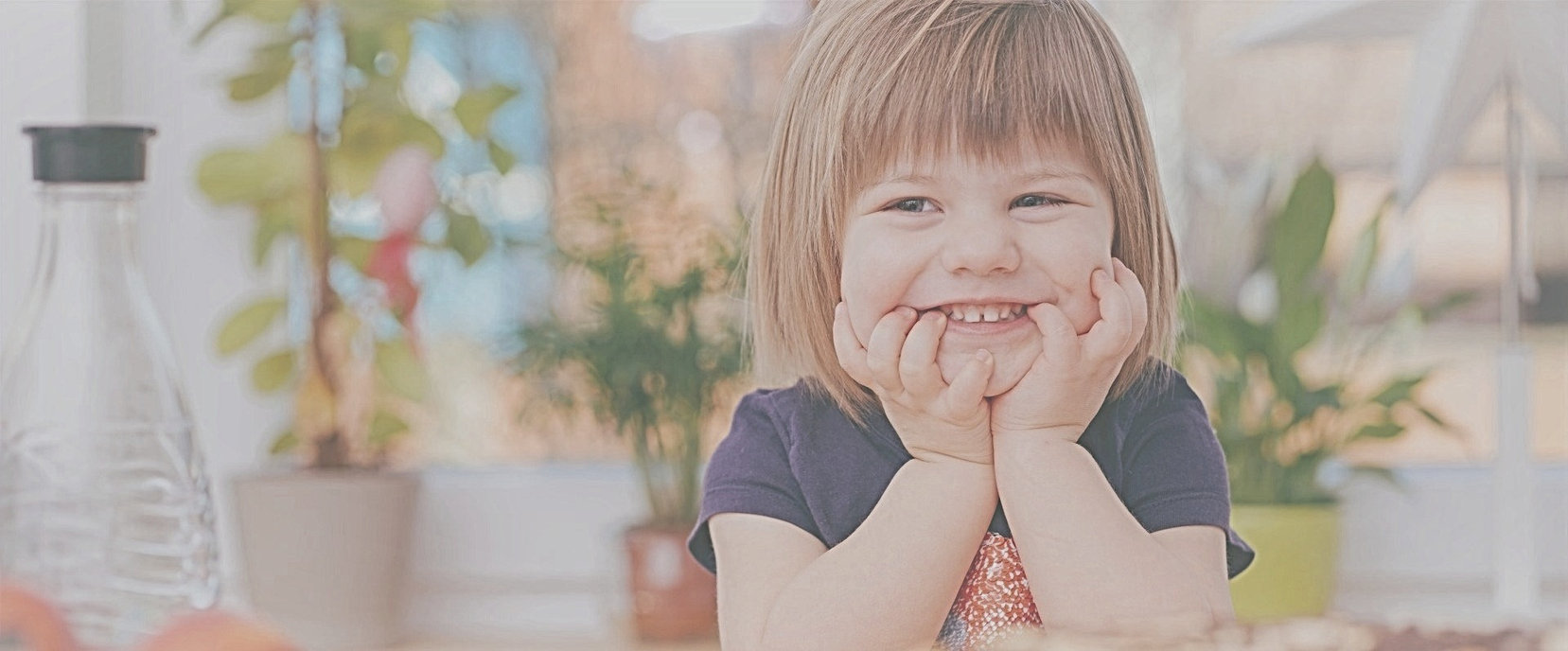 toddler-touching-her-face-while-smiling
