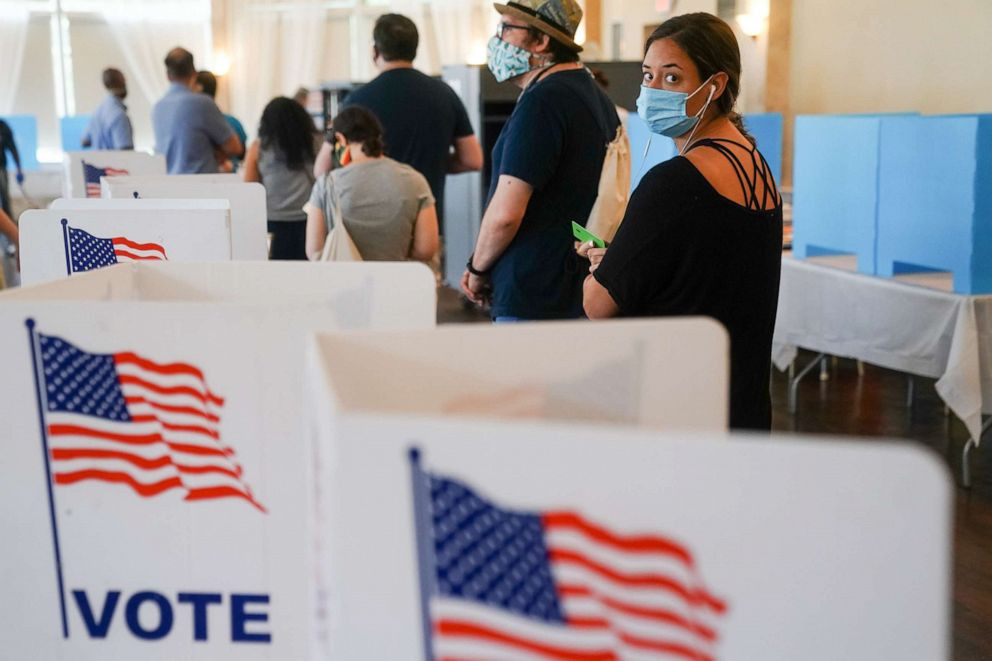 Voters wear masks and socially distance at a polling place (Photo Credit: ABC News)