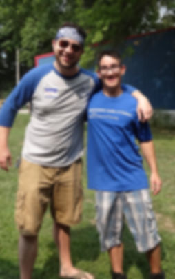 Adult with sunglasses has arm around teen boy in glasses