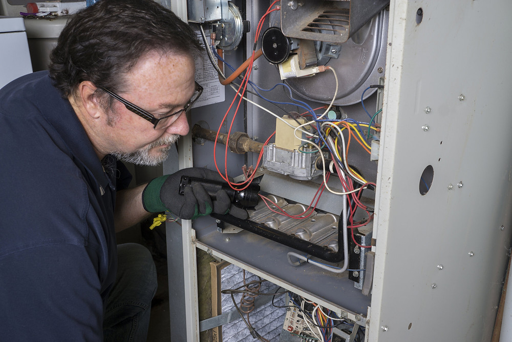 An HVAC technician working on a furnace.