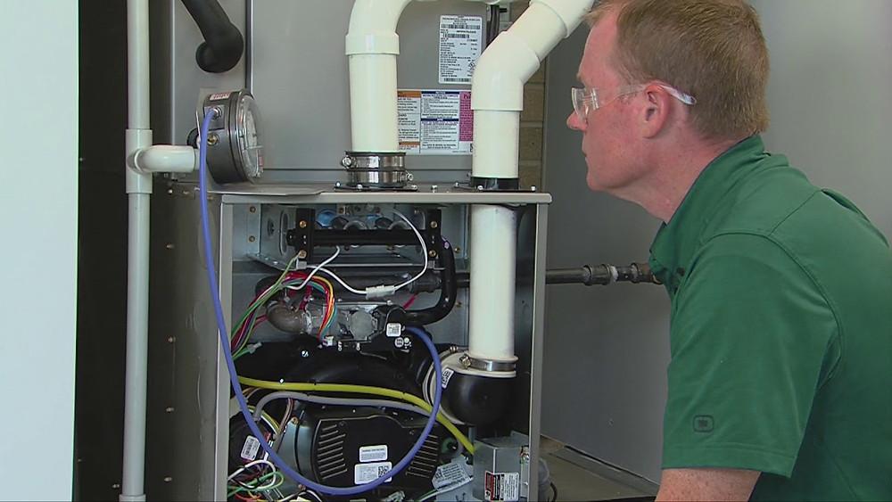 An HVAC technician working on a furnace.