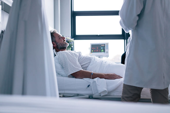 Sick man lying in hospital bed with doctor.jpg Male patient getting treatment in hospital.jpg