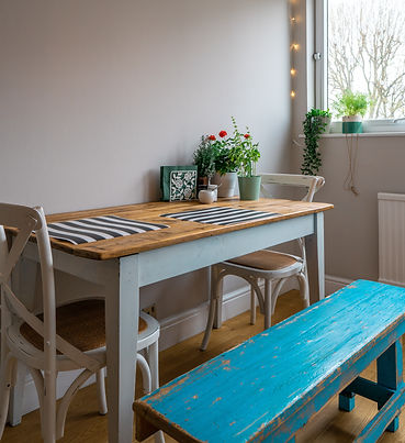Kitchen table with flowers and bench