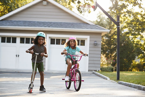Two girls riding bikes in their driveway