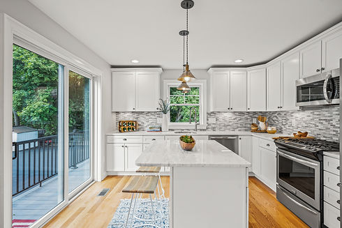 Kitchen with white marble countertops and slider to the deck