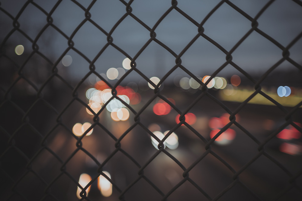Chain link fence with bokeh lights in the background