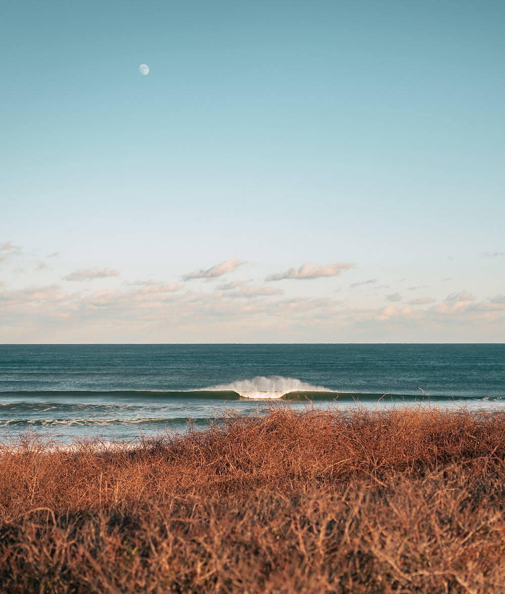 The moon hangs low over the ocean as a nice swell comes in off the Cape