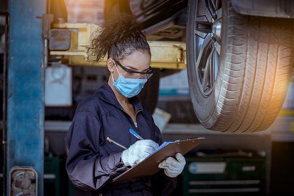 Car mechanic under checking car wheels a