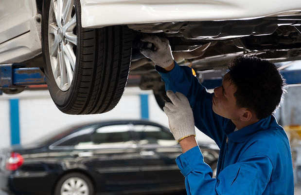 Mechanic fixing car suspension with car