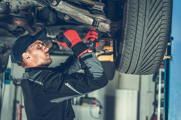 Caucasian Car Mechanic Adjusting Tension