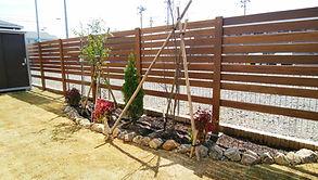 木製フェンスの高さは、地面から1,650㎜とし、リビングから庭を眺めても外の視線を気にすることなく寛げる空間になっています。木製フェンスの板張りは、下まで全面張るのではなく、あえて下側の空間をあけておくことで、日差しが花壇に届くように設計しております。地面には姫高麗芝を敷き、ガーデニンググッズを収納できる物置も設置しました。