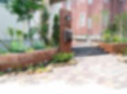 自然石の花壇と木製の門柱、枕木階段、レンガのインターロッキングブロックの洋風エントランス