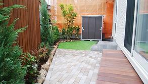 リビングからお庭を眺めた際に、ハードウッドで作った木製支柱やコニファーが目隠しとなり、安らぎを感じ取ることが出来ます。お庭のコーナーには、シンボルツリーとして大きなイロハモミジを植え、その脇には、春の息吹を感じ取れるように、アメリカハナズオウ(シルバークラウド)とハナミズキを植えています。玄関前のアプローチの乱形石張りは、住宅のカラーにマッチするようにダンディな色合いのものを選定。サイクルポートは、ぎりぎり軽自動車もカバーできるサイズのものを設置しました。