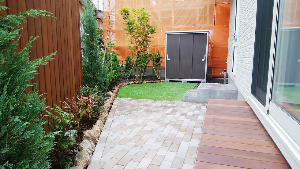 縁台とインターロッキングブロックのテラス、人工芝生と物置
