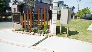 入り口に乱形石張りを用いたゆるやかなS字曲線のアプローチ。段差ステップを斜めに配置することで、道路から玄関までの自然な動線をもたらします。門壁はリビング側に向けて斜めに配置することで、アプローチを通る人の視線を遮る役目を果たしています。また、脇には宅配ボックスも設置しました。門塀前花壇の自然石(ミカモ石)の配置は、アプローチのS字曲線のつながりとの連続性を持たせています。自然石を使用することで、ナチュラルな感じのエクステリアになります。セランガンバツ支柱の間に設置したロートアルミフェンスは、アプローチから眺めた際に、奥のシンボルツリーや根元の草花が見えるようになっています。インタ-ロッキングテラスの脇に家庭菜園スペースを作ることで、リビングからの出入りを容易にし、作業しやすくしています。