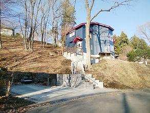 施工前は傾斜地に設置された丸太の簡易階段でした。安全面で不安がありましたので、コンクリート製の階段を作成し、手すりを設置して安全・安心な階段アプローチを作成しました。駐車場も、普通車と軽自動車が2台並列に駐車出来るように設計し、夜間でも安心して駐車出来るように照明も完備!斜面の土砂は、擁壁ブロックでしっかりブロックしています。