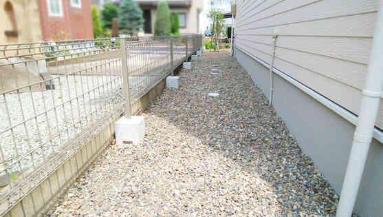 犬走りのフェンスと砂利