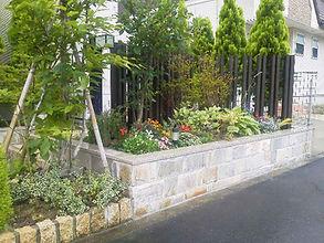 玄関脇の花壇とお洒落なアプローチは、繊細な質感と色合いで表情豊かなデザインに仕上げました。花壇と統一したウリン材のガーデンアーチがお洒落です。テラスの真っ白なイタリア製のタイルと御影石の照明枠が上品なお庭です。