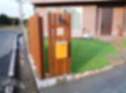 木製フェンスの門柱、人工芝のお庭